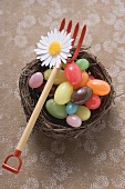 Coloured sweets in an Easter nest with toy pitchfork