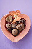Chocolates in heart-shaped dish (coloured background)