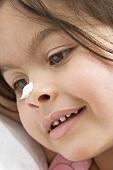 Hübsches Mädchen mit Creme auf der Nase (Porträt)