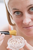 Woman putting on make-up (powder pearls)