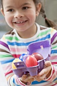 Girl with coloured Easter eggs in an egg box