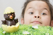 A girl with a chocolate chick hatching out of an egg