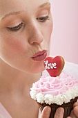 Young woman kissing a cupcake (Valentine's Day)