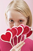 Young woman with several heart-shaped lollipops