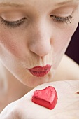 Young woman kissing red chocolate heart