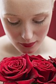 Young woman smelling red roses