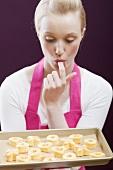 Young woman with a baking tray of freshly-baked biscuits