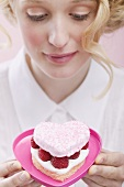 Young woman holding raspberry cake in heart-shaped dish