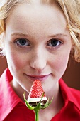 Young woman with a chocolate-dipped strawberry