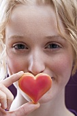 Young woman holding a heart in front of her mouth