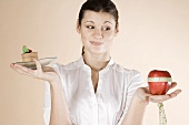 Woman holding chocolate cake and apple with tape measure