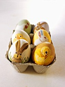 Easter eggs painted with animal motifs in egg box
