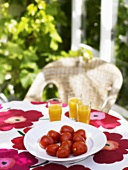 Tomatoes and orange juice on a table out of doors
