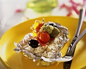 Fish fillet with pesto, tomatoes & olives on aluminium foil