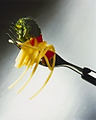 Spaghetti and vegetables on fork