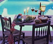 Tisch mit Käseplatte, Oliven, Weissbrot und Rotwein am Pool