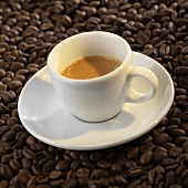 A cup of espresso on coffee beans