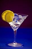 A glass of Martini with ice cubes and lemon slices