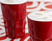 Coffee with milk froth in red beakers