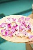Hand holding a tray of flower petals at a swimming pool