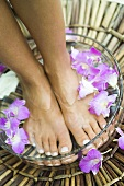 Woman bathing her feet in a bowl of flower petals