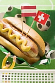 Sausage with mustard in bread roll, flags & football figure