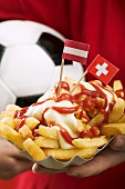 Chips with ketchup and mayonnaise, flags and football