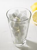 Sugar cubes in tumbler, lemons in background