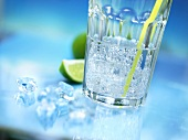 A glass of mineral water with straw, crushed ice and lime
