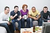 Freunde mit Fussball, Bier und Pizza sitzen vor dem Fernseher