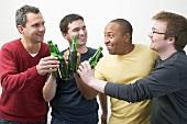 Four men clinking bottles of beer