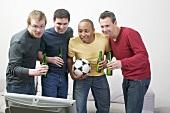 Vier Männer mit Bierflaschen und Fussball vor dem Fernseher