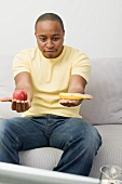 Young man with apple and banana watching TV