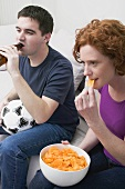 Young couple with football, bottle of beer & crisps watching TV