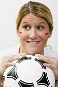 Young woman with German colours on her face holding football