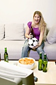 Young woman with football and bottle of beer watching TV