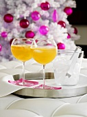 Orange drinks with ice cubes, Christmas tree in background