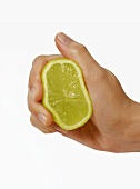 Hand lightly squeezing half a lime