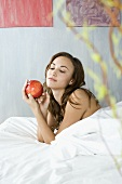 Young woman with a red apple in bed