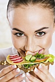 Young woman eating open sandwich on wholemeal bread