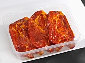 Marinated pork collar steaks in plastic container
