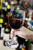 Hand hält ein Glas Rotwein, im Hintergrund Weinflaschen