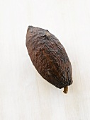 A cacao fruit on white wooden surface