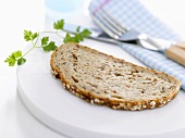 A slice of granary bread with chervil and cutlery
