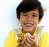 Boy with paintbrush in his mouth holding Easter eggs in his hands