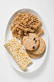 Wholemeal pasta, wholemeal biscuits & muesli bars on plate