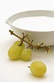Skin cream in white dish with white grapes