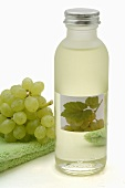 White grape seed oil and white grapes on towel
