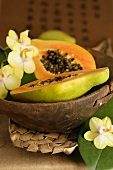 Halved papaya with orchid flowers in wooden bowl