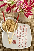 Bowl of Asian noodles with chopsticks and flowers